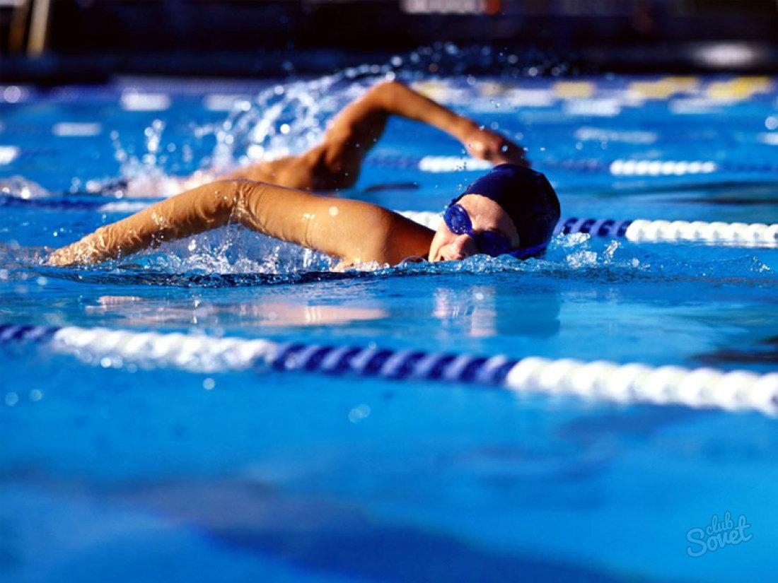Девушка плавает по дорожке в бассейне