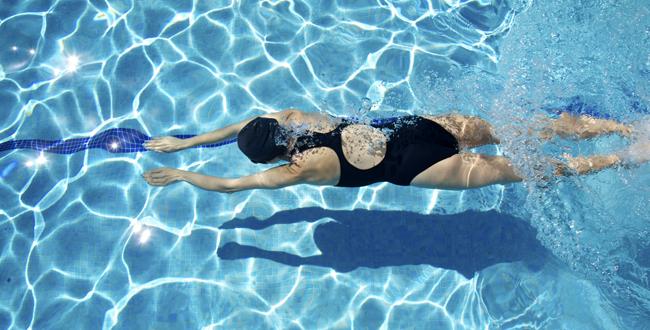 Девушка занимается плаванием в бассейне