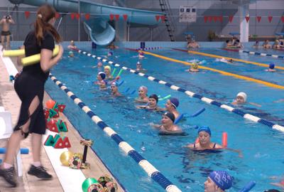 Занятие аквааэробикой с инструктором в бассейне