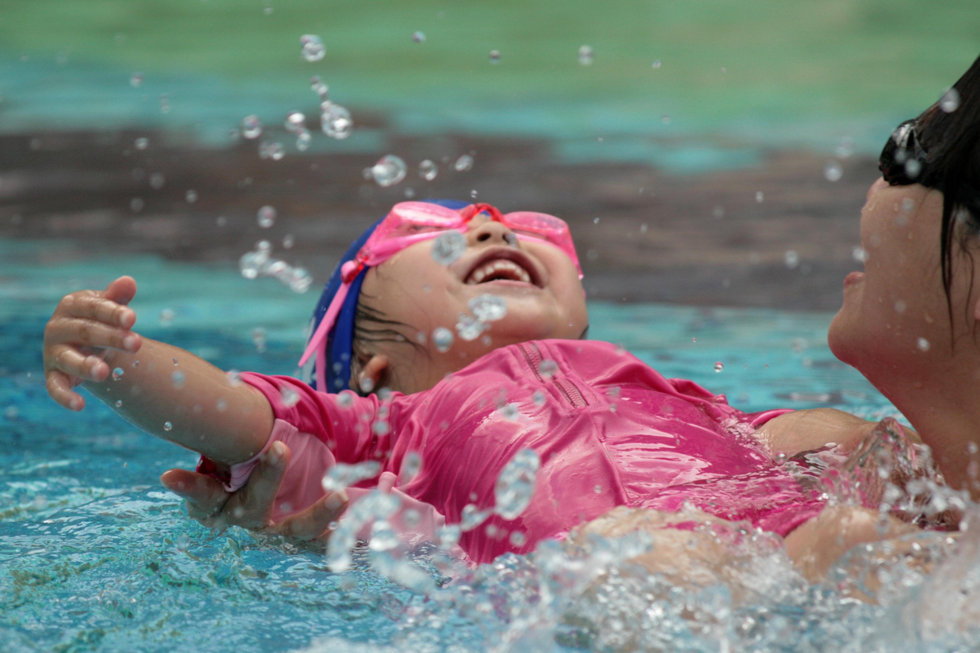 Ребенок учится плавать в бассейне