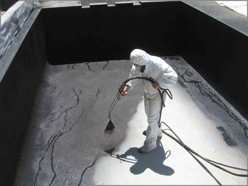 Строитель выполняет работы по гидроизоляции бассейна