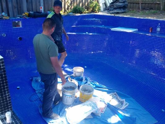 Строители выполняют работы по гидроизоляции бассейна