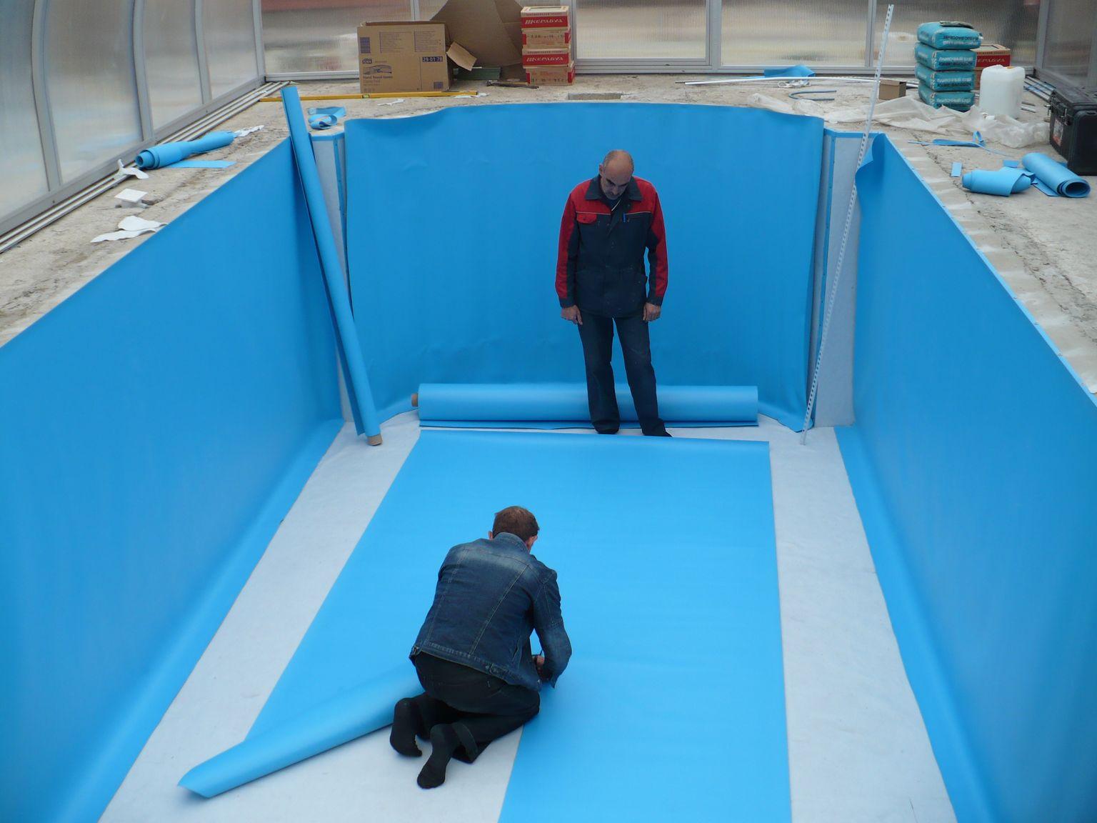 Рабочие проводят гидроизоляцию бассейна с помощью ПВХ-покрытия