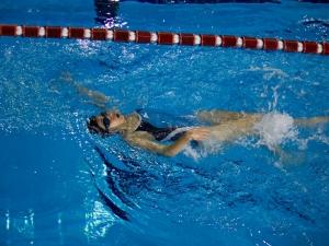 Спортсмен плывет кролем на спине
